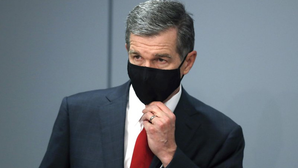 Gov. Roy Cooper adjust his mask as he listens to Dr. Mandy Cohen, secretary of the North Carolina Department of Health and Human Services, speak during a briefing at the Emergency Operations Center in Raleigh. (Ethan Hyman/The News & Observer via AP)